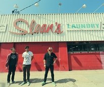 together PANGEA band standing in front of Sloan's Laundry