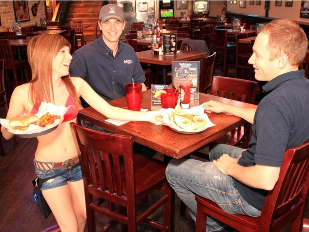 A waitress serves customers at Bikinis Sports Bar