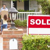 sold sign in front of house with family moving boxes inside