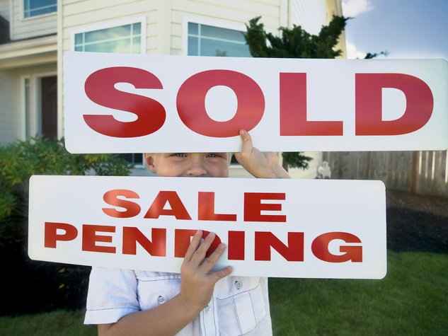 house sale pending sign sold sign young boy