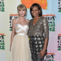 Michelle Obama wears jacket by Wes Gordon and poses with Taylor Swift