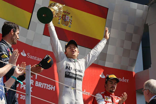 Nico Rosberg of Germany celebrates his victory on the podium with Mark Webber and Fernando Alonso.