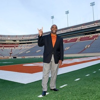 Coach Charlie Strong giving hook 'em at DKR Stadium