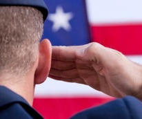 veteran military man saluting an American flag