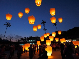 flying paper lanterns released into night sky