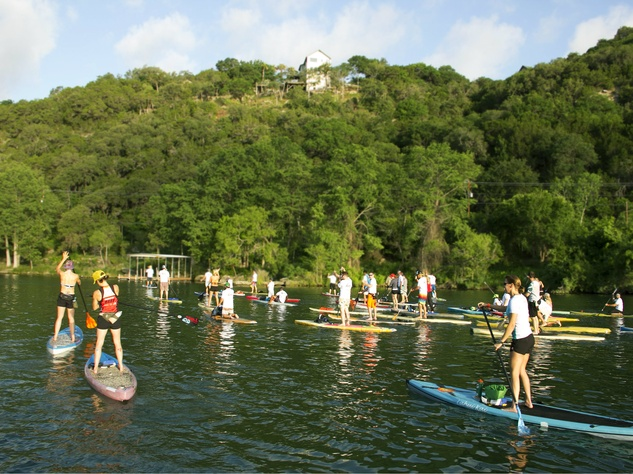 group of paddleboarders on lake austin for tyler's dam that cancer
