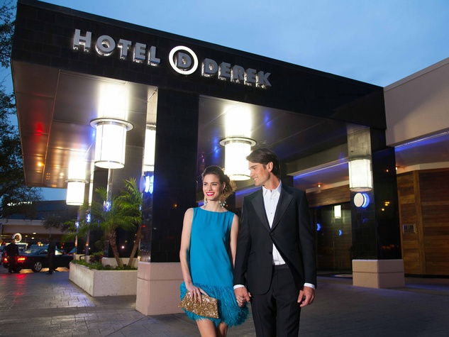 Hotel Derek couple walking outside hotel at night