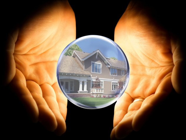 crystal ball with house in it being held by hands