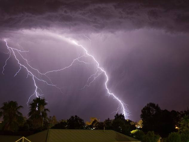 lightening in dark sky over rooftops of houses