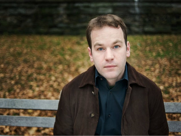 Comedian Mike Birbiglia headshot sitting on park bench