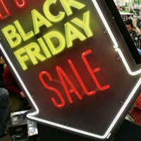 Black Friday neon sign and shoppers