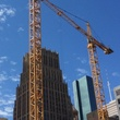 Construction cranes work under a blue October sky over Main Street in downtown Houston October 2014
