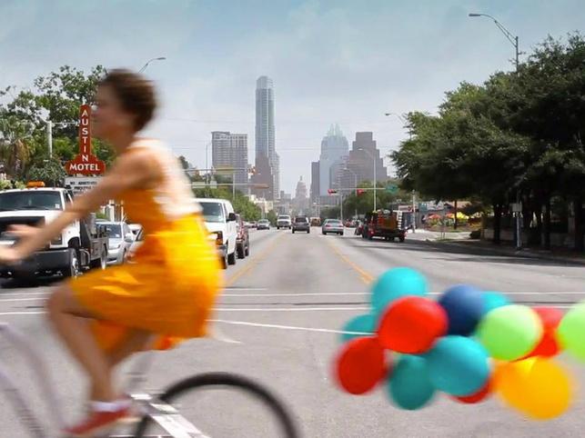 Amplify Austin funraiser woman bike bicycle baloons South Congress Avenue