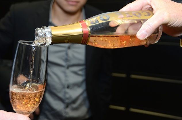 164 Pouring a glass of Bottle of Cote Or gold-flecked champagne at the Red Carpet Soiree November 2014
