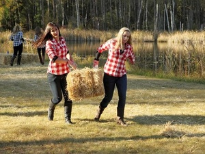 Girls carry bales of hay on the Bachelor