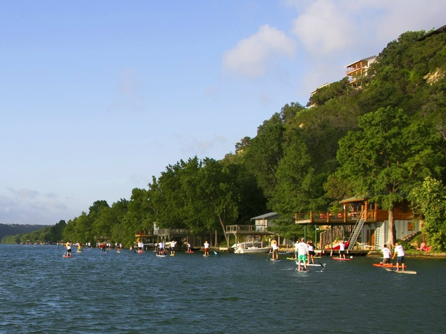paddleboarders on lake austin in front of hill