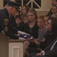 Elyse Lanier recieves flag at funeral of Bob Lanier