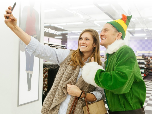 Elf posing with shopper for selfie