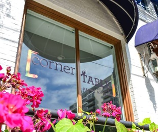 Corner Table exterior with sign and flowers