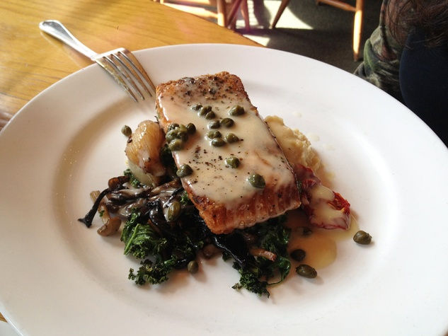 Trenza curried lemon caper sauce over pan-seared salmon with mushrooms and kale