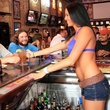 Bikinis Sports Bar & Grill waitress in bathing suit top serving guys at bar