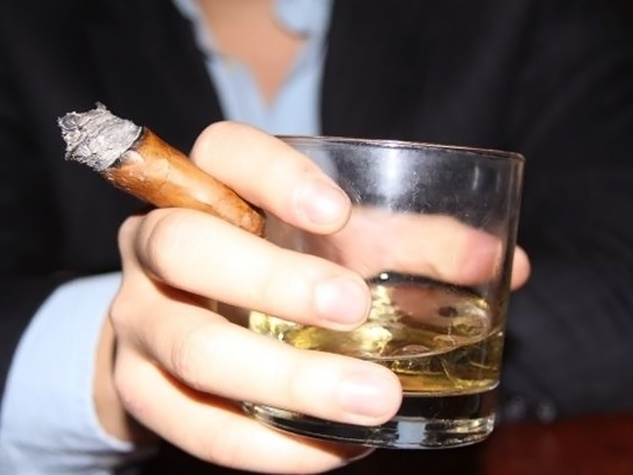 Downing Street Pub & Cigar Bar man's hand holding whiskey and cigar