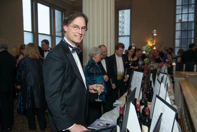 219 Dr. Gary Brock perusing action items at the Houston Symphony Wolfgang Puck wine dinner March 2015