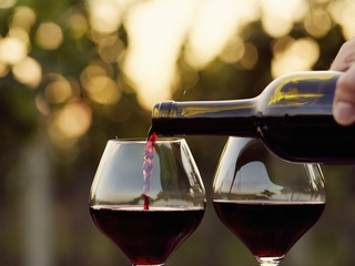 Two glasses of red wine being poured
