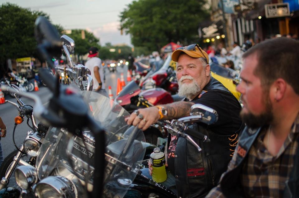 rot rally Medicine Man and Hoss watch bikers ride down Sixth Street, Saturday evening.