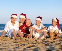 Kids on the beach wearing Santa hats