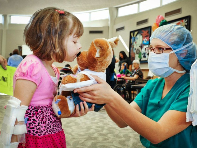 """Patient Madeline Smith, 10, gives her teddy bear a kiss before it is taken in for """"surgery"""" by Child Life fellow Leah Dunn"""