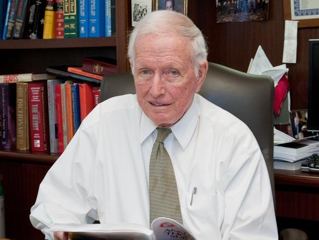 Dr. Denton Cooley at desk with bookshelf behind him