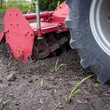 Photo of tractor wheel and tines on a tiller
