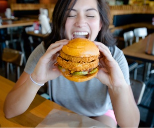 Woman eating the Lockhart Legend burger