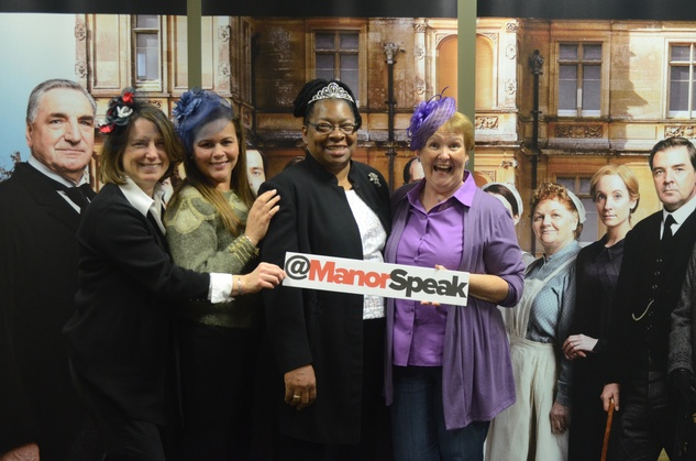 Elaine Roach, Carol Lukes, Rhonda Onwere, Irene Brackenridge pose in front of wall of Downton Abbey characters