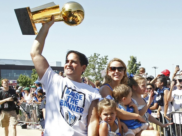 Mark Cuban raises the NBA championship trophy