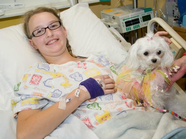 TSRHC patient Lydia, age 11 of Greenville, Texas; TSRHC volunteer Micki Jenkens (red) holding Kristal, a Maltese, 13