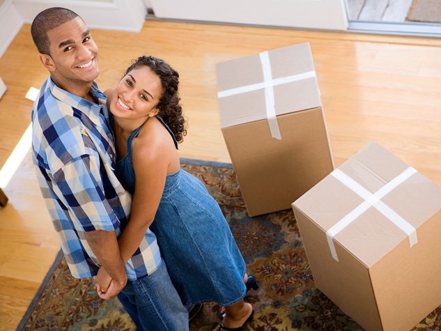 young couple with boxes moving into new house