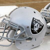 Oakland Raiders football helmets on bench
