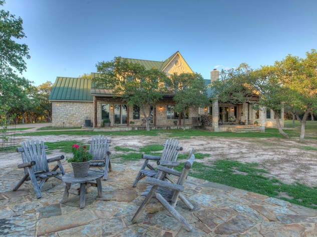Red Adair ranch home exterior with patio chairs