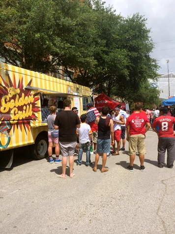 Fans at food truck at Lucky's Pub for USA vs. Belgium soccer game.