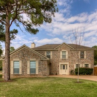 median home in Houston house front with pine trees and lawn