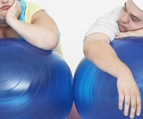 fat couple trying to exercise with balls