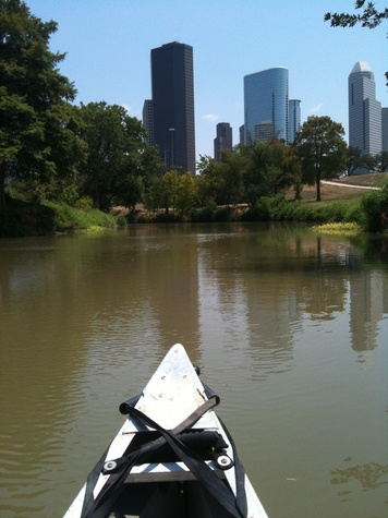 Buffalo Bayou with canoe in foreground and skyline in background
