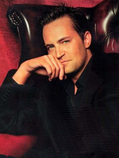 Matthew Perry in leather chair with red background