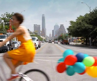 Amplify Austin funraiser woman bike bicycle baloons South Congress Avenue