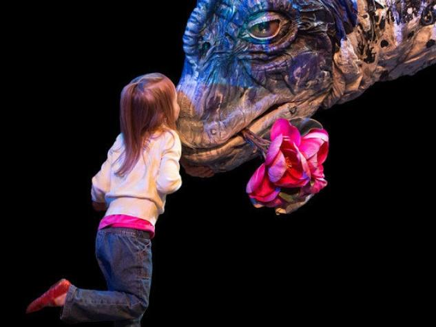 little girl kissing brachiosaurus at Erth's Dinosaur Petting Zoo
