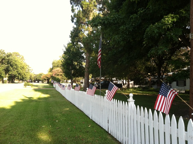 American flags on a white picket fence