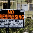 No Trespassing Violators will be prosecuted sign on fence